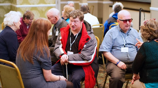 A group of people at a meeting some of whom have sight loss